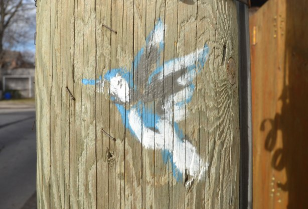 On a wood telephone pole, a small bird painted in white, black and blue.