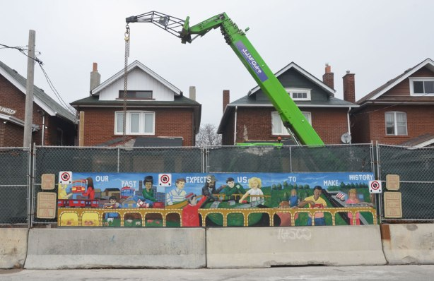 mural in front of a construction site, the tops of two brick houses are visible behind the fence, a large green crane is working at the site