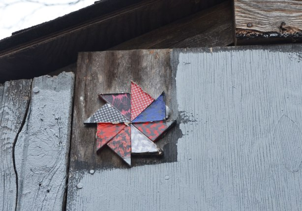 8 sided pinwheel in reds and blues fixed against the top corner of a shed or garage wall in a lane