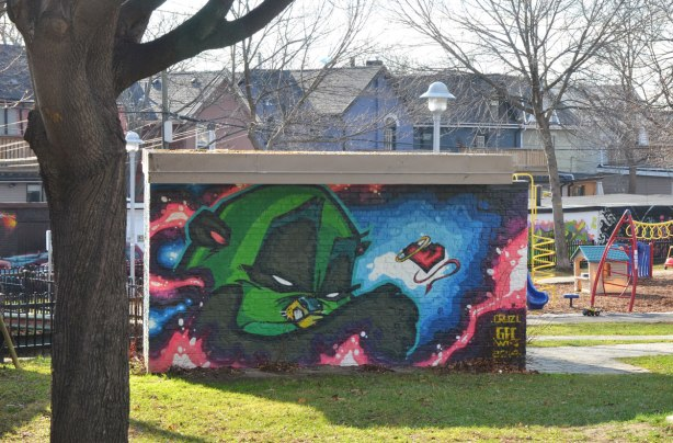 side of a small building covered with a mural of a green bird-like character, playground and houses in the background