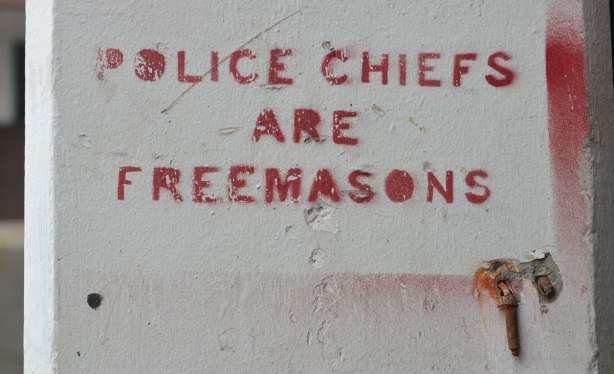 stencils on concrete, in red, words that say: Police Chiefs are Freemasons