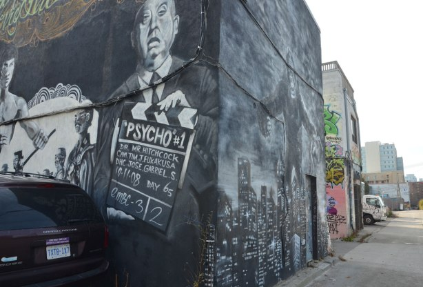 part of a larger mural, Alfred Hitchcock holding a sign for the filming of Psycho, Bruce Lee is also in the picture, a car is parked in front of the wall, in an alley