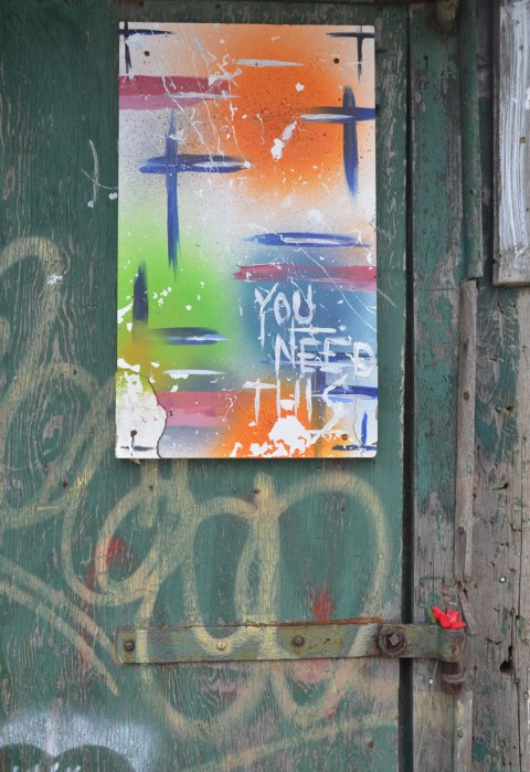 An abstract painting with the words you need this written on it. below, tucked into the hinge of the door is a plastic red rose