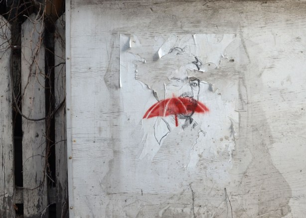 A drawing of a man on white paper pasted to a concrete wall. A red stenciled umbrella is on top of his face. A white picket fence is beside the wall.