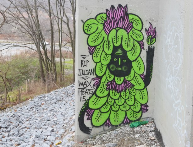 graffiti on concrete bridge supports - creature with black face and covered in green leaves, with a few purple petals on top of the head. words, RIP Julian Waxhead