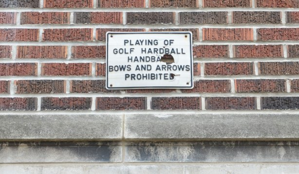 old sign on the exterior wall of a school that says: Playing of golf, hardball, handball, bows and arrows prohibited