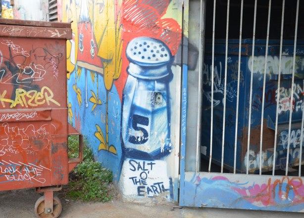 graffiti street art in an alley - a large salt shaker with the words Salt o' the Earth written below it. A garbage bin is beside it.