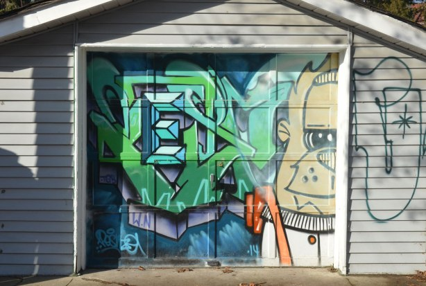 garage door with street art on it, half of a large man plus green and blue tag around the letter E