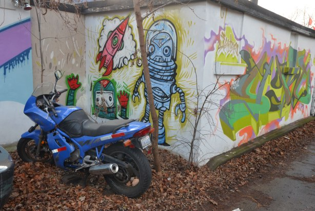 A blue motorcycle is parked in front of a street art painting of three spacemen creatures