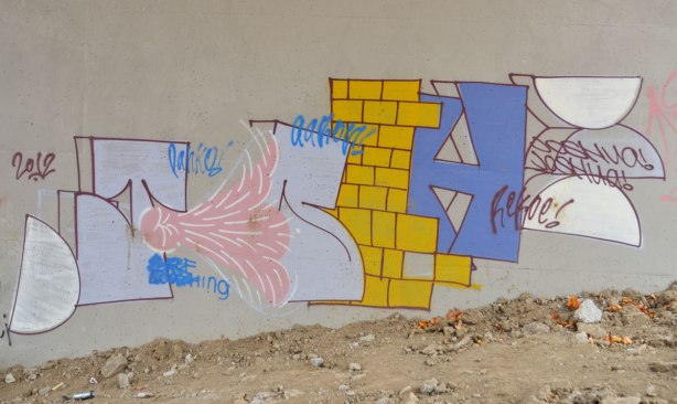 graffiti on concrete bridge supports, block letters