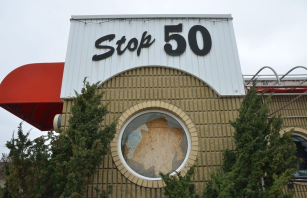 Stop 50 sign over a round window at the entrance to the office of the motel, now abandoned. The window has been broken, then covered from the inside.