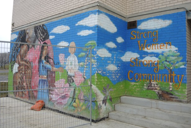 Strong Women, Strong Community are the words written on a mural, people painted on a wall