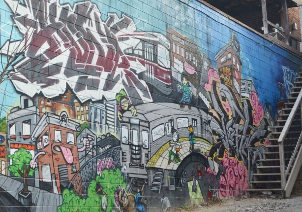 mural on the side of building in an alley, TTC streetcar, buildings, people, subway,