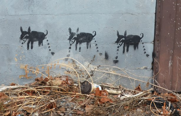 stencil of three small animals walking across the lower part of a grey garage door.