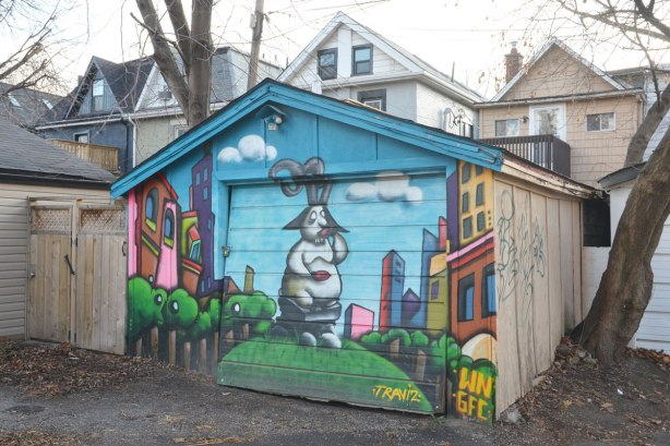 Garage door covered with a mural by traziv. Rabbit like creature standing on a grass mound eating a carrot. buildings around hime, blue sky and a fluffy cloud too.