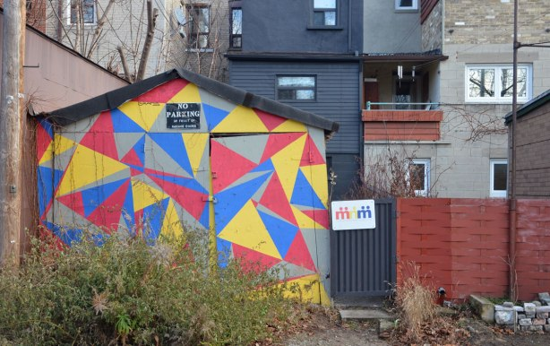 old garage door painted light grey with triangles in blue, yellow and red