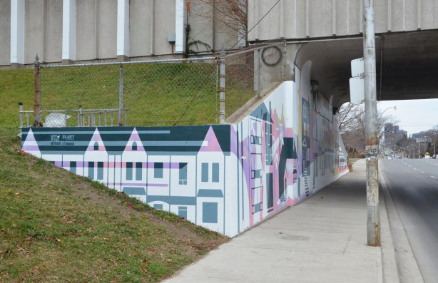 part of a mural by Rob Matejka and Tommy Matejka on the wall on a TTC subway underpass at Keele, a mural of houses on a street, south corner