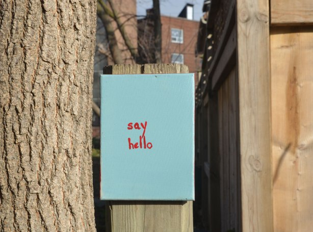A small canvas painted turquoise and the words say hello written in small red letters, attached to a fence in a lane