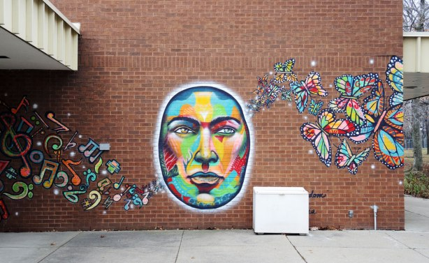 A brightly coloured mural on a brick wall. A large oval face with music symbols on the left and butterflies on the right. Called united freedom and painted by essencia.