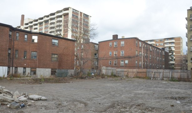 vacant lot with a number of low rise brick apartment buildings in the background.