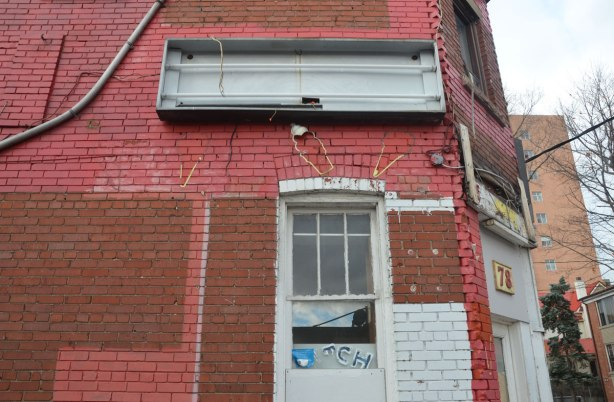 side of a brick building that used to be an ice cream store. Painted red with some white parts, front has been removed from lighted signs, exterior decorations have been removed except a faint outline of ice cream shapes remain above the window.