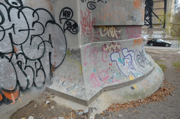 On the Bayview Extension, a black car drives under the Bloor Viaduct, past concrete supports with graffiti on them.