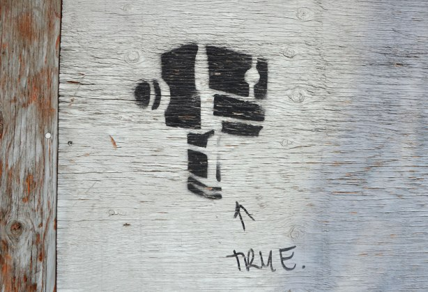 black stencil of an old fashioned video camera. Someone has written the word true under it.