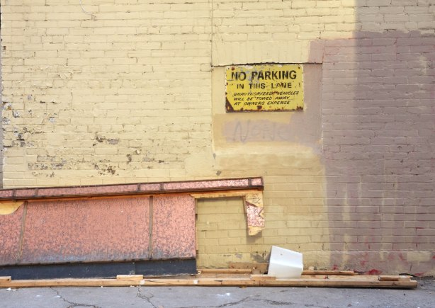 A light yellowish grey wall with a yellow sign that says no parking. Old sign, looking worse for wear. A piece of flat scrap metal is leaning against the wall