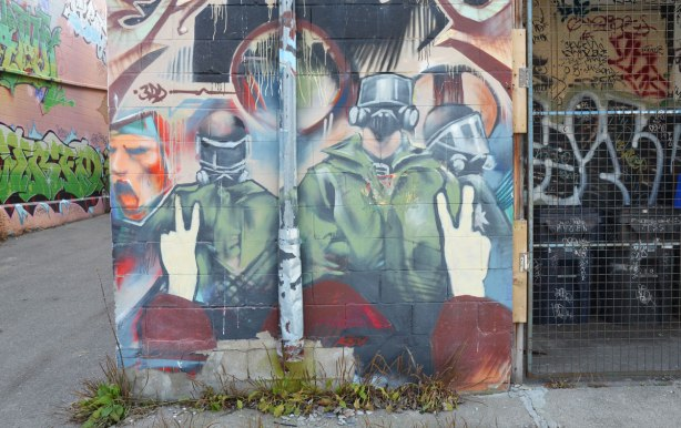 mural of police in riot gear confronting a person with both hands giving a peace sign