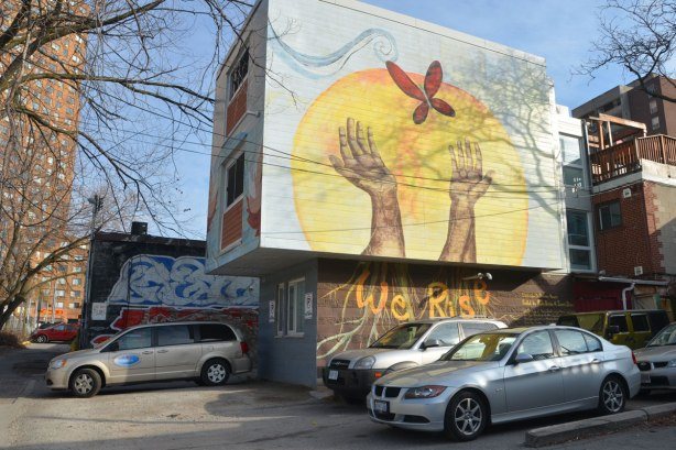 large mural of upreached open hands releasing a red butterfly