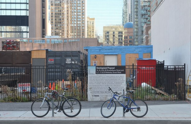 two bicycles parked on a sidealk in front of a fence that has a development proposal sign on it. Building site behind that, thena wall of skyscrapers in the background.