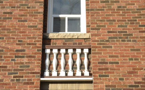A white framed window in a red brick building. Below the window are a few white pieces of wood that look like a balcony railing even though there is no balcony there.
