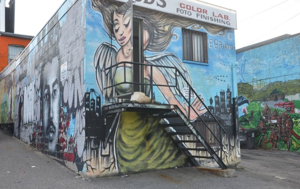 a large mural of a woman with wings that takes up the entire back of a two storey building in a laneway. There is also a metal staircase with a small porch. The door at the top is open so part of the woman in the mural opens up too. The mural is by EGR art.