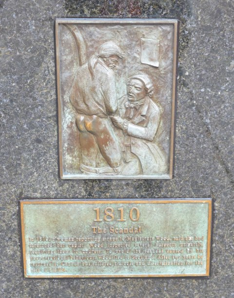 plaques on a statue. The top is of a man with his pants lowered, the bottom is the story of the scandal that led to Alexander Wood having to leave Canada.  The bare bum on the plaque is shiny from repeated rubbing by passers by.