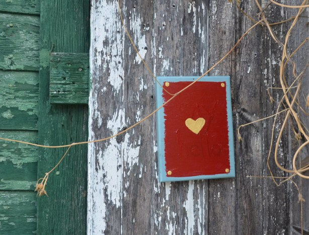 A small canvas painted red and a small yellow heart painted in the middle. The words say hello are painted on it too but they are harder to see. It is nailed to an old wood fence
