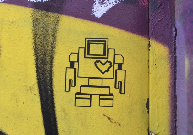 black line drawing of a lovebot on a yellow section of a graffiti picture on a garage door in a laneway