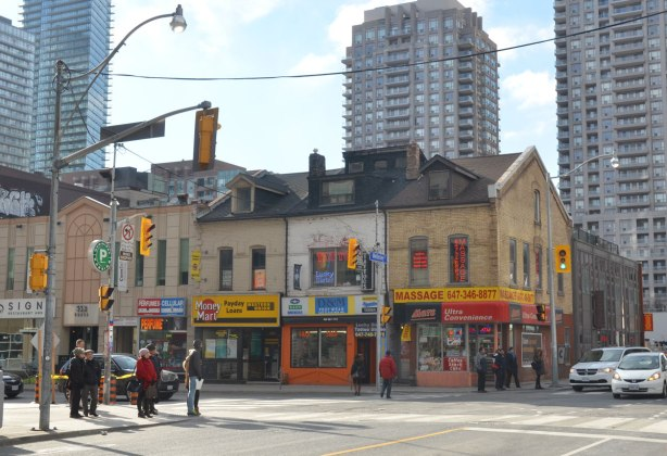 southwest corner of Yonge and Wellesley, a row of old buildings, now storefronts. A Massage parlor and a tattoo place, a convenience store and a Money Mart. Gass condos in the background.