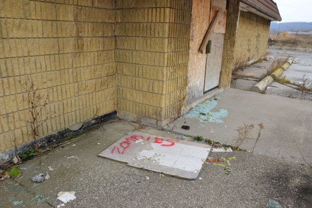 Outside the boarded up doors of a motel, broken glass, a piece of wallboard with some one inch tiles still attached on which someone has spray painted the word zombie in red
