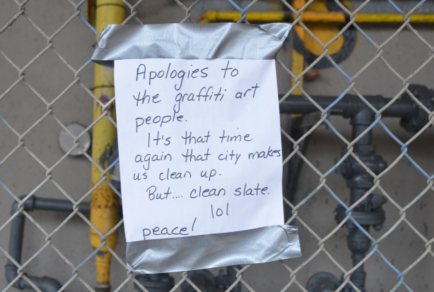 hand written sign duct taped to a chain link fence that reads: Apologies to the graffiti art people. It's that time of year again that city makes us clean up. But... clean slate 101. Peace.