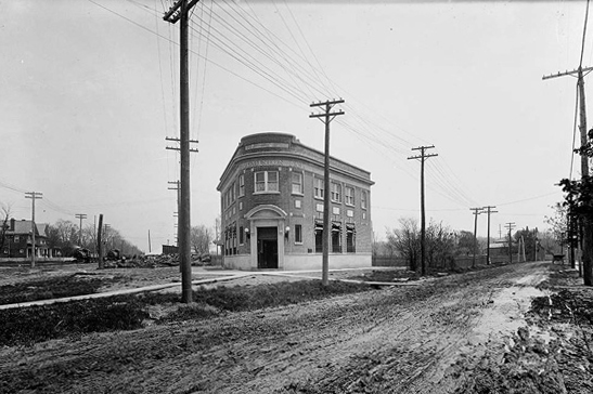 Historical black and white photo of a two sorey brick building at an intersection of two dirt roads.