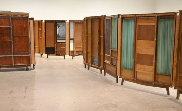 part of an art installation by Chinese artist Song Dong using vintage wooden wardrobe doors with mirrors and curtains, reflections