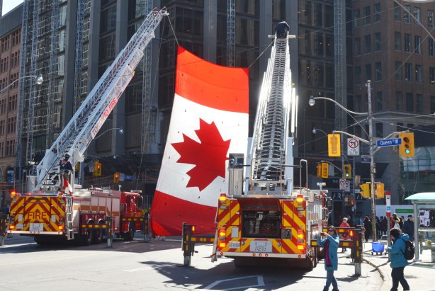 A very large Canadian flag hangs from the cranes of two fire trucks at the corner of Queen and Bay streets in downtown Toronto