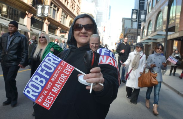 A woman in hoodie and sunglasses holds two small Ford Nation flags as well as a bobble head doll of Rob Ford as she walks in his funeral procession down Yonge Street