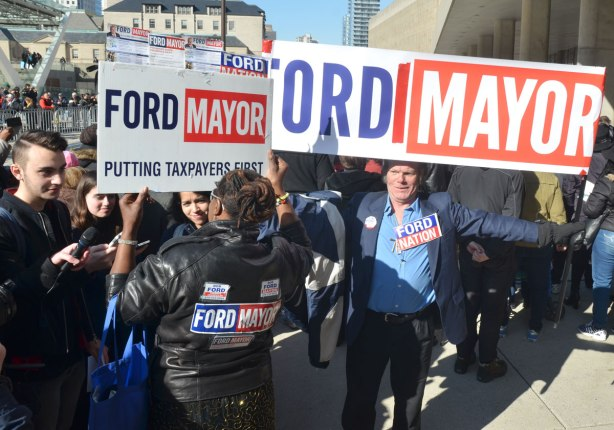 A middle aged man holds a banner that reads Ford Mayor over his head, beside him is a woman also holding a Ford Mayor sign. On the back of her jacket are a number of stickers in support of Ford