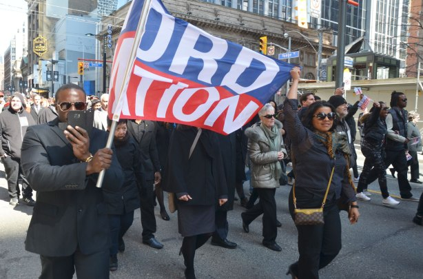 A man and a woman are each holding the side of a Ford Nation banner as they walk with a group of people in the procession to Rob Ford's funeral