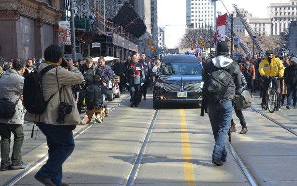 A funeral procession for Rob Ford passes along Queen Street on its way to St. James cathedral, photographers are in front, a police guard is walking beside it.