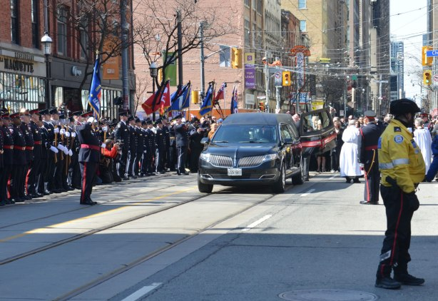 The hearse carrying Rob Ford's body arrives at St. james cathedral and the casket is taken out and carried into the church with police honour guard