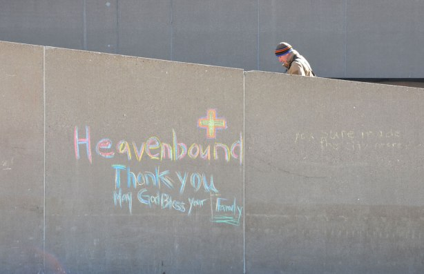 A man walks up the concrete ramp at City Hall, beside him on the wall is written in chalk, Heavenbound. Thankyou. May God bless your family.