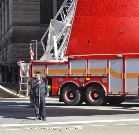 A fireman holds a rope that is attached to the corner of a very large Canadian flag. A firetruck is behind him
