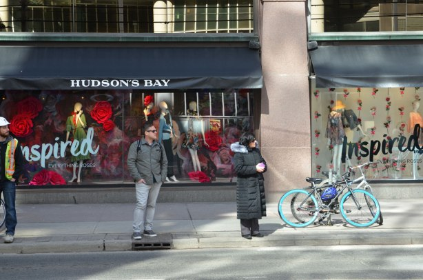 Three people stand on the sidewalk in front Hudsons Bay store windows. A man with a hard hat, a man with hands in his pockets, and a woman in long black coat. A couple of bikes are parked there too. The theme of the store windows is Inspired.